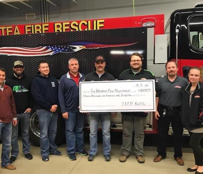 SERVPRO team presenting donation to Tea Fire Department
